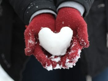 Snow heart in gloved hands